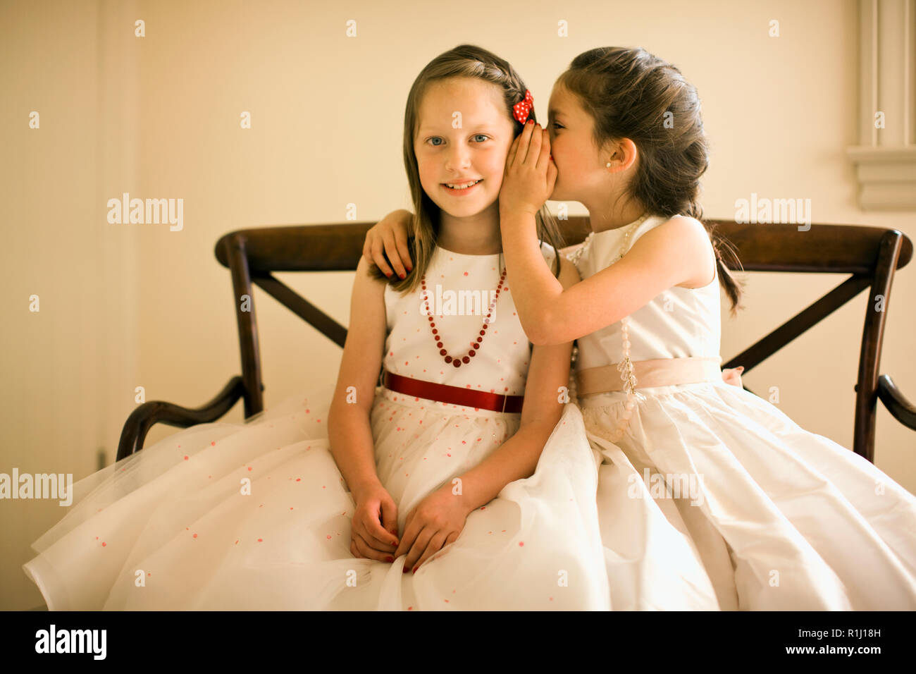 Young girls in white party dresses sit on wooden bench and whisper secrets as they pose for a portrait. - Stock Image