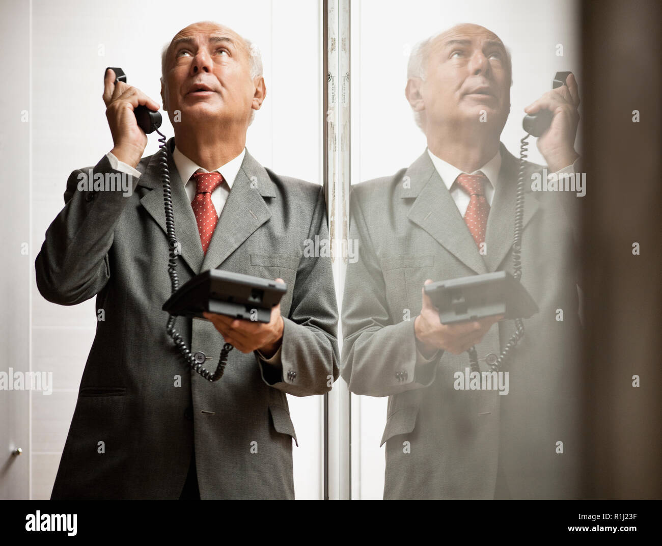 Senior businessman on a stressful phone call. - Stock Image