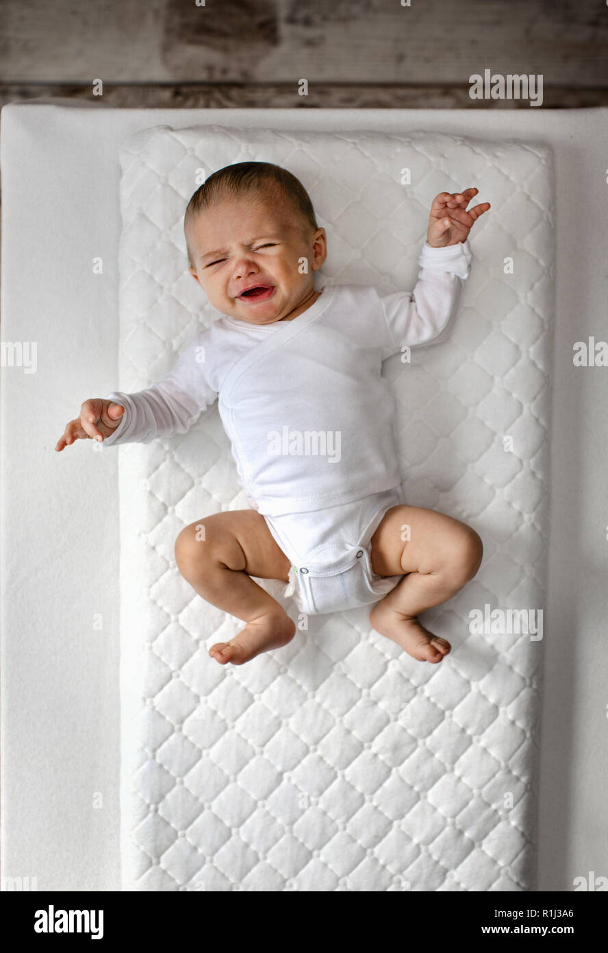Crying baby lying on changing table. - Stock Image