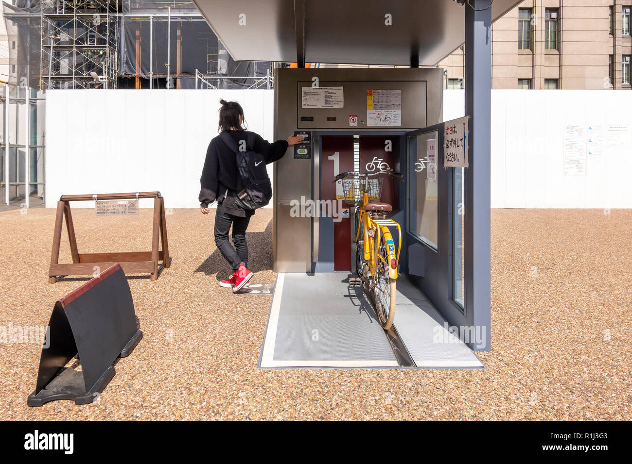 Girl parking her bike in a Giken Eco Cycle automated underground bicycle parking in front of Kyoto City Hall, Japan. Series of 3 images - Stock Image