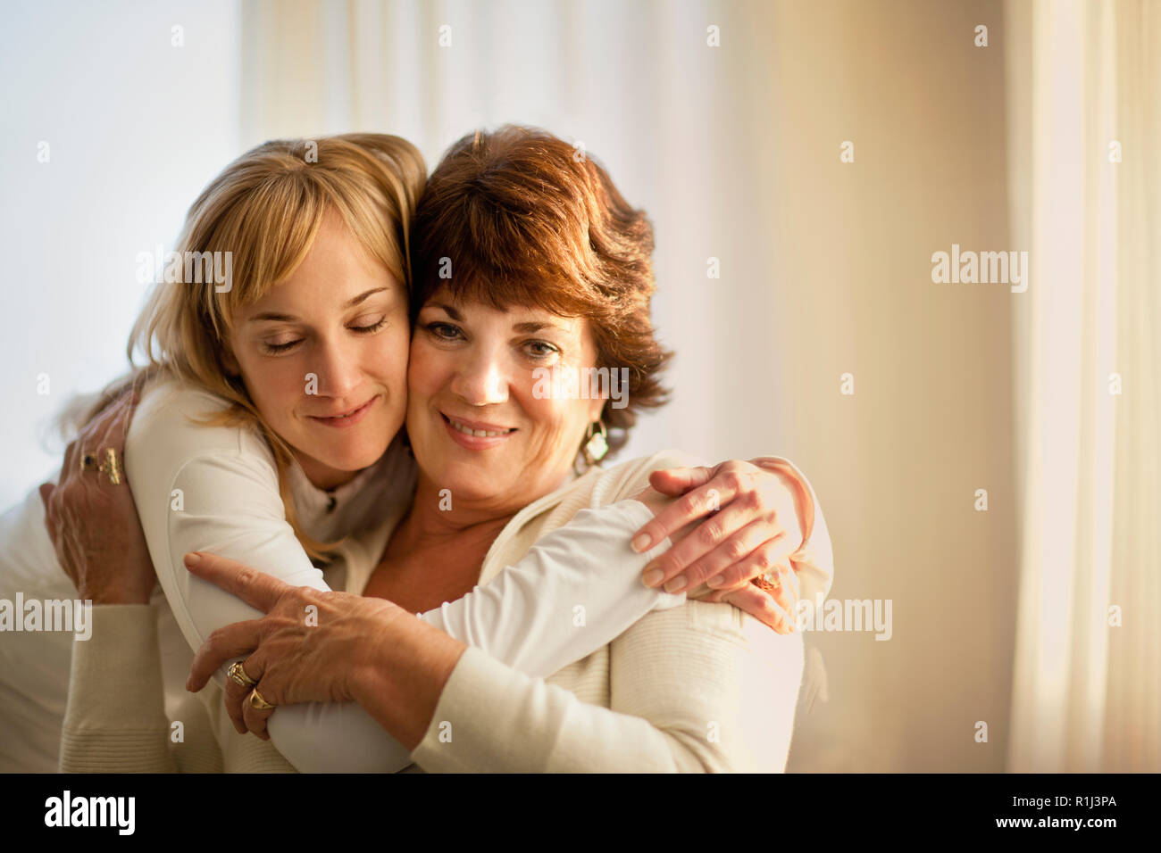 Portrait of a mature woman being hugged by her adult daughter. Stock Photo