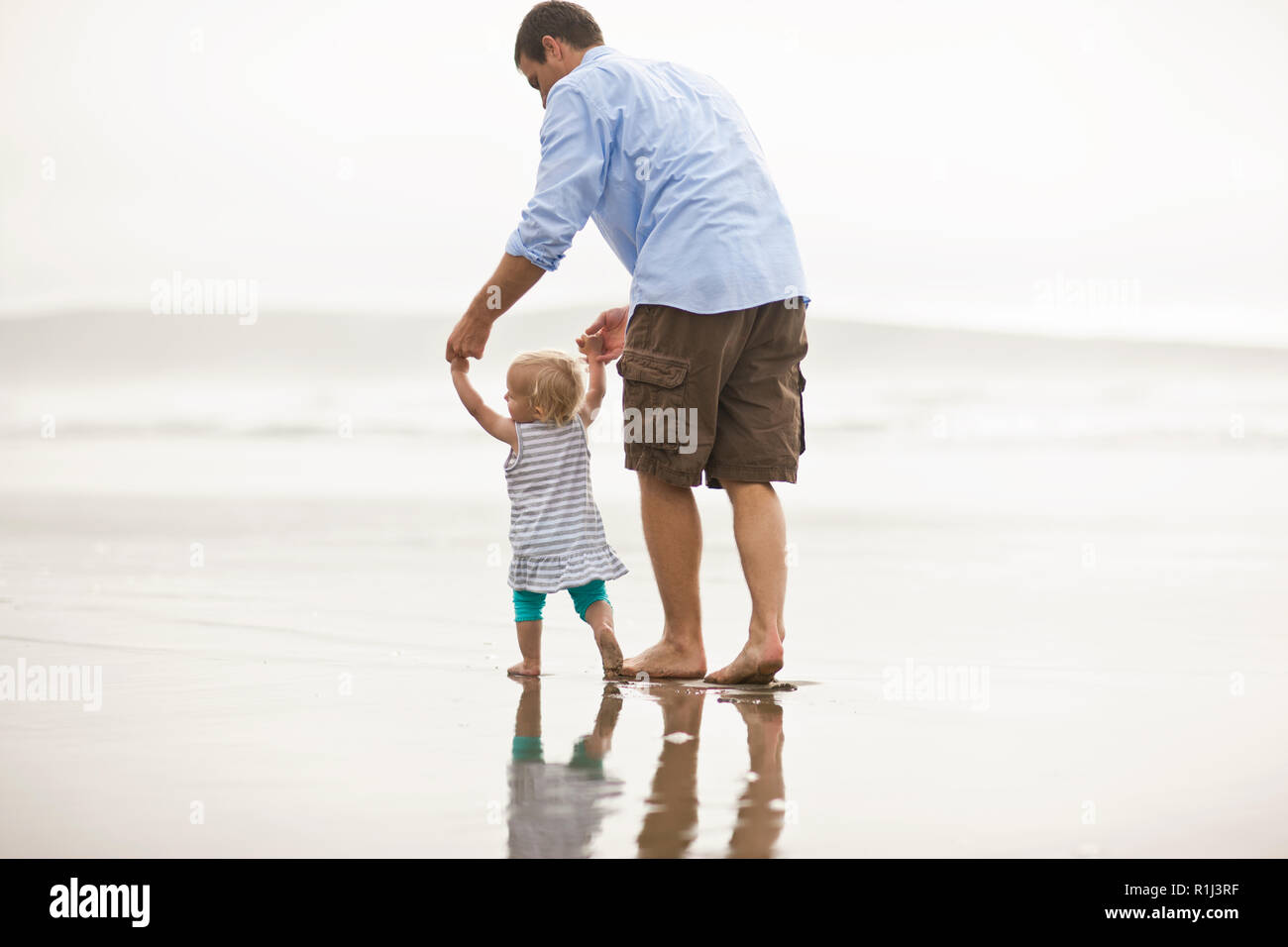 Father helping his baby daughter take her first steps on a beach. Stock Photo
