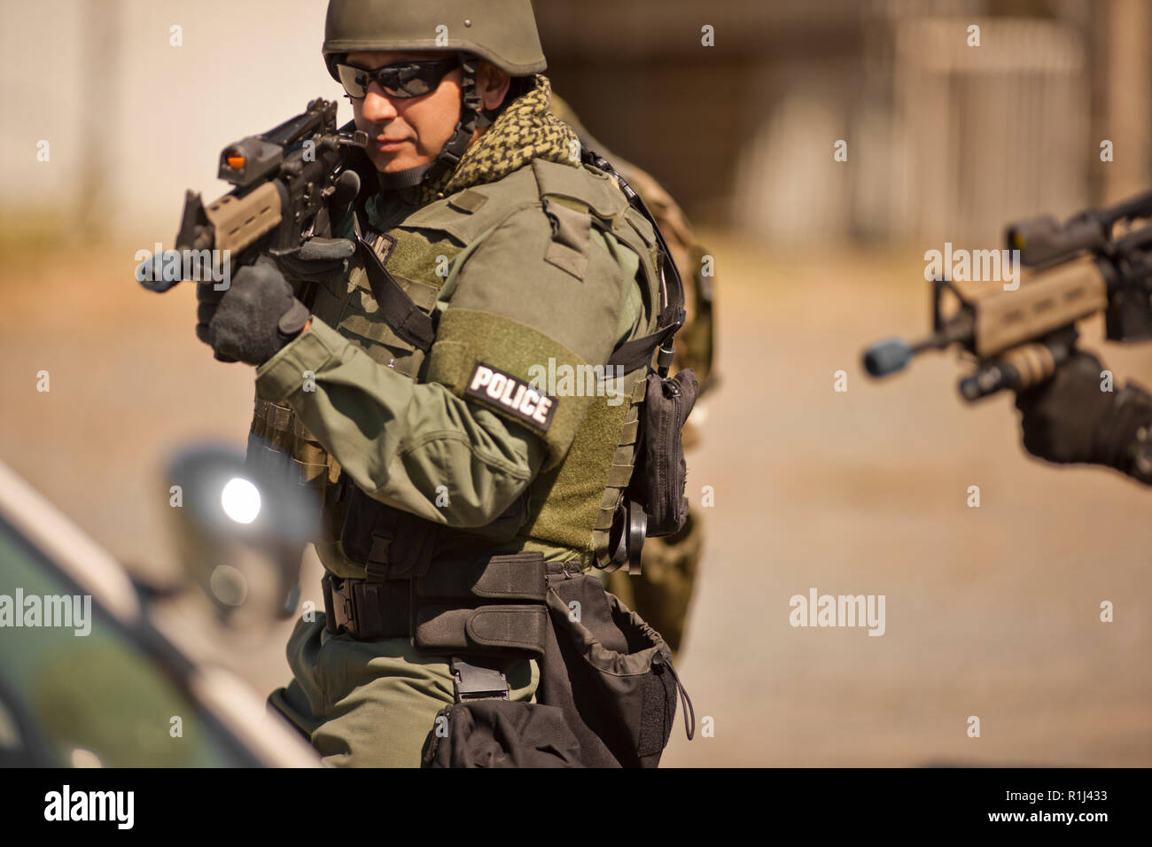 Male police officer aiming a gun toward a target during an exercise at a training facility. - Stock Image