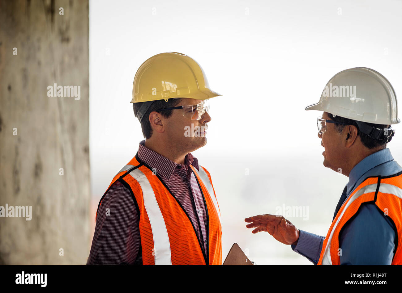 Two construction managers talking on building site. - Stock Image