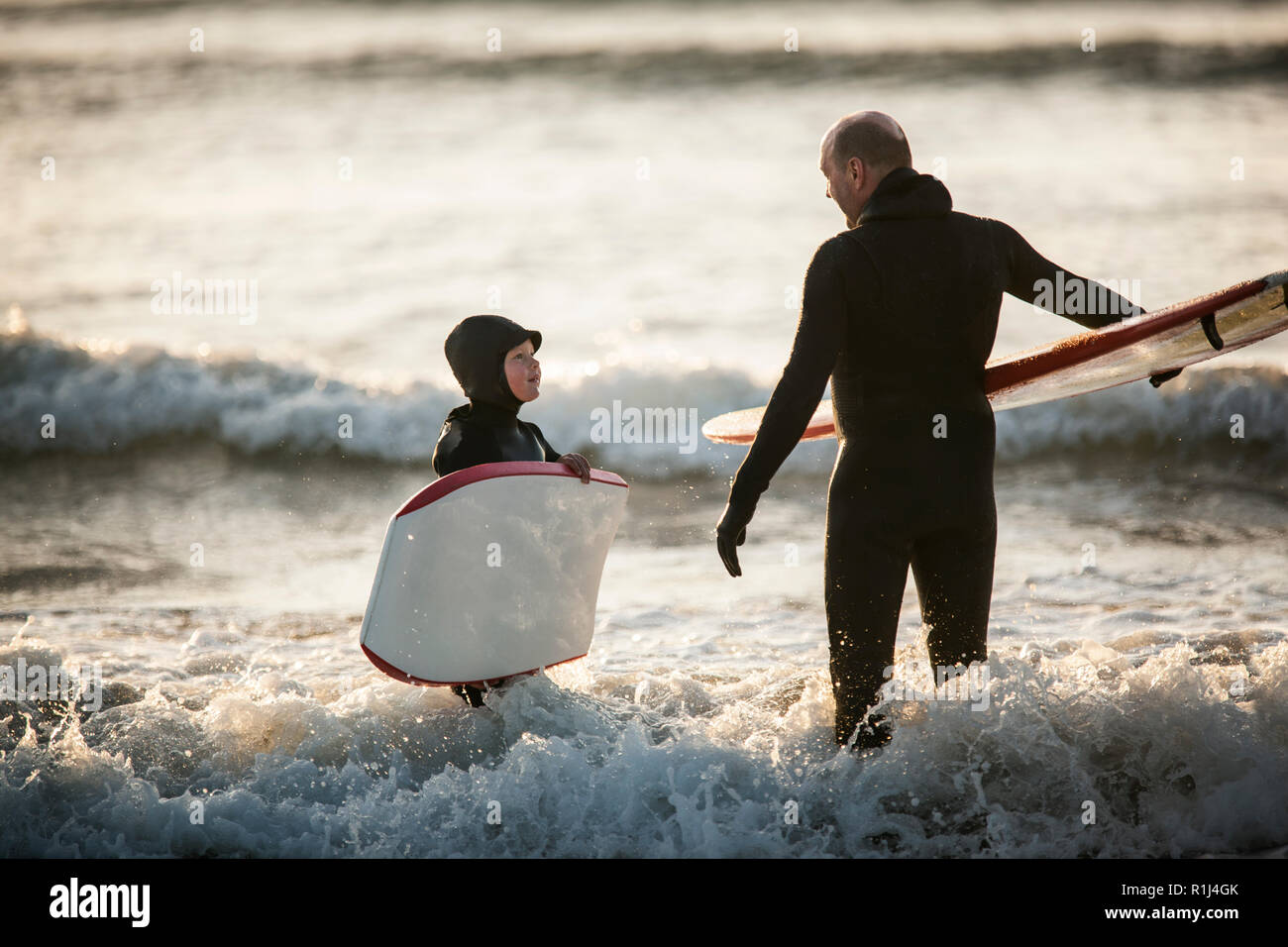 Mid adult man and his young son having a conversation while standing in shallow water holding their boards at the beach. Stock Photo