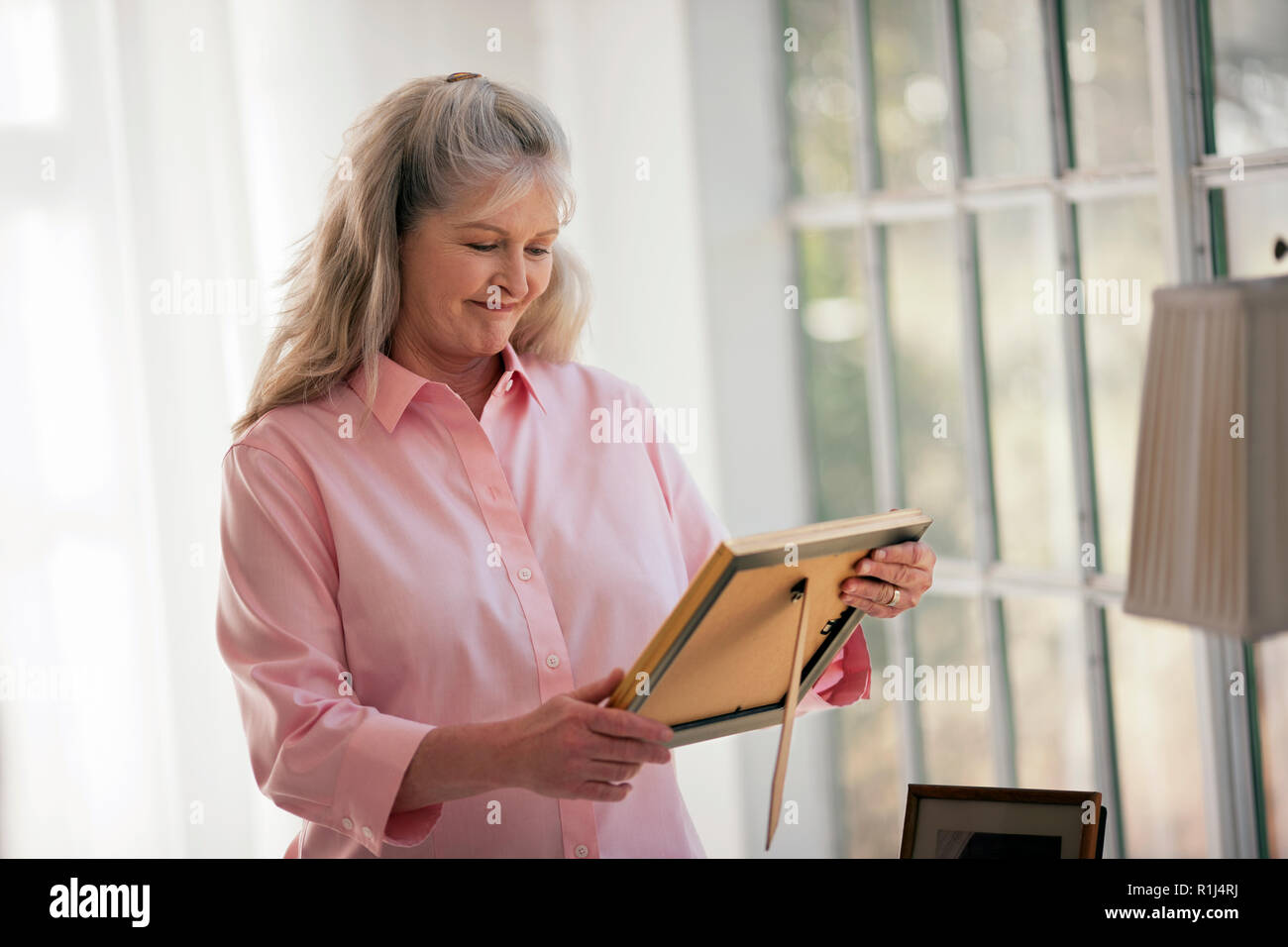 Happy mature woman looking at old family photos. - Stock Image