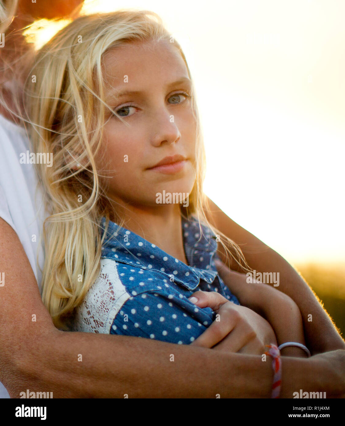 Portrait of a teenage girl leaning against her mother. Stock Photo