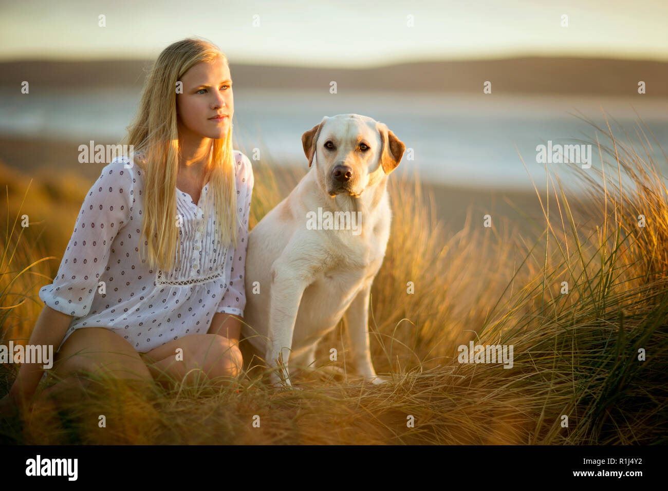 Teenage girl sitting in a grassy sand dune with her dog. Stock Photo