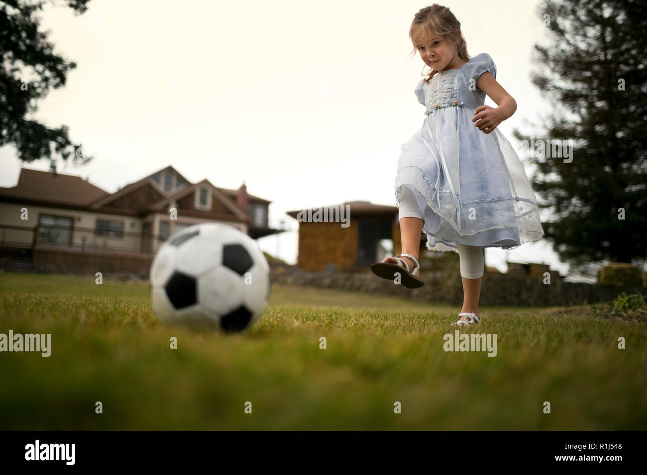 Smiling little girl in a dress has fun kicking a soccer ball on the grass. Stock Photo