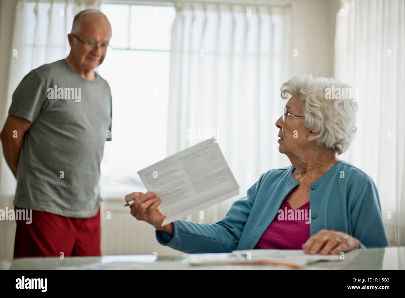Elderly woman asks her worried husband about a bill they have received. - Stock Image