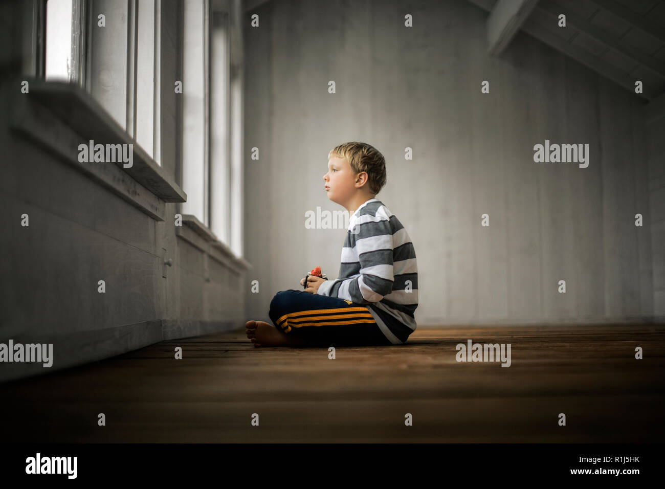 Young boy looking thoughtfully out a window. - Stock Image