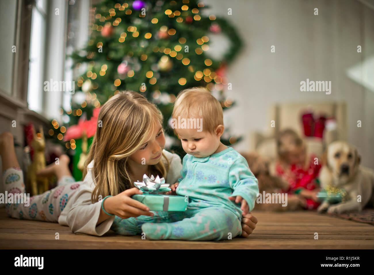 Young girl giving her baby sister a Christmas present. - Stock Image