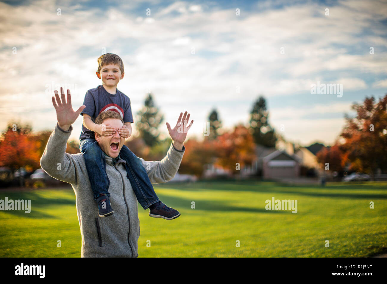 Boy having piggyback ride on his father's shoulders. - Stock Image