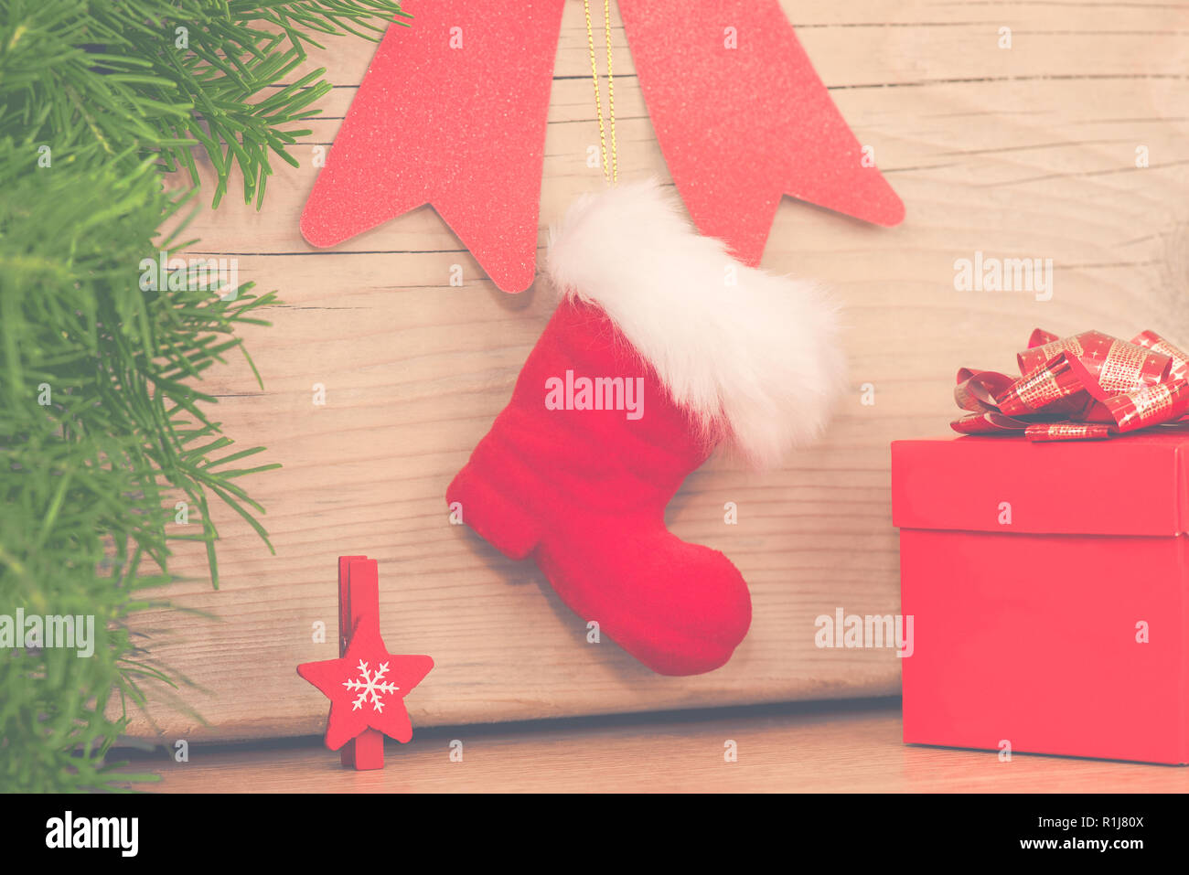 Christmas arrangement with red boot, gift and wooden star - Stock Image