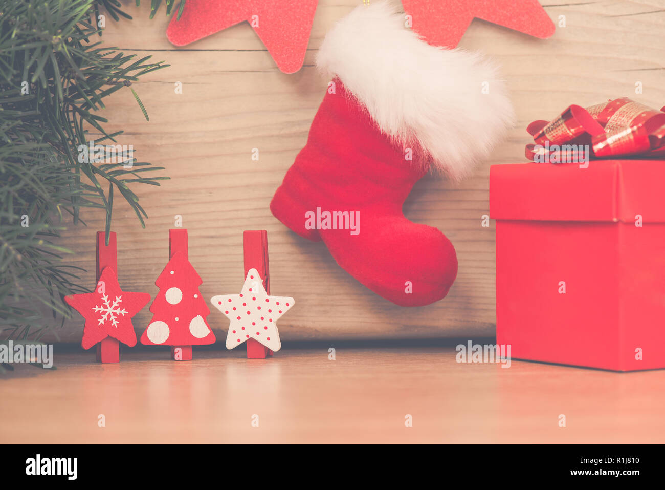 Christmas arrangement with red boot gift and wooden stars and fir tree - Stock Image