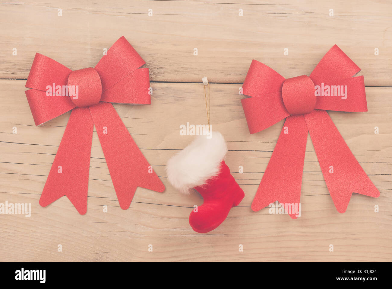 Christmas arrangement with red boot and two red bows on wooden background - Stock Image