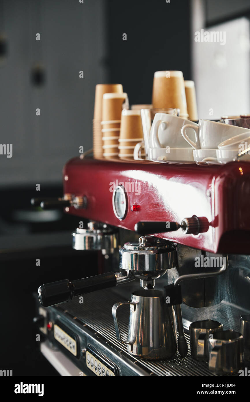 professional coffee machine with mugs and paper cups in coffeehouse - Stock Image