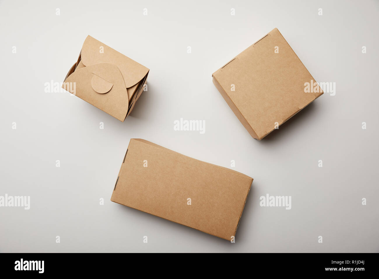 Top View Of Wok Box And Food Delivery Boxes On White Surface Stock