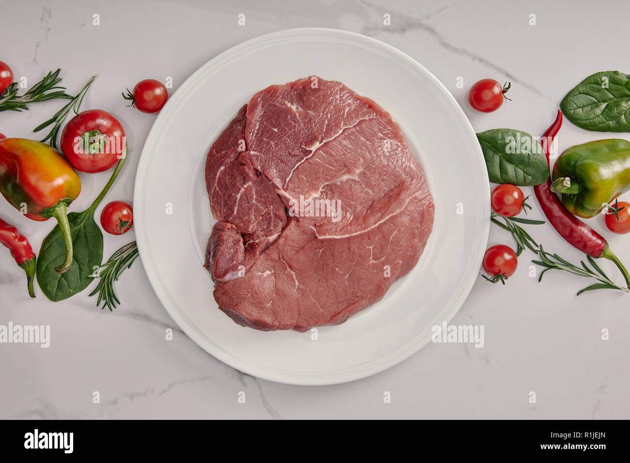 top view of fresh raw meat on plate with vegetables and herbs on white background - Stock Image