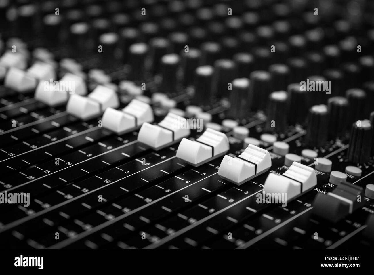 Low level view of Faders on a Professional Audio Sound Mixing Console at music festival, black desk and white Faders - Stock Image