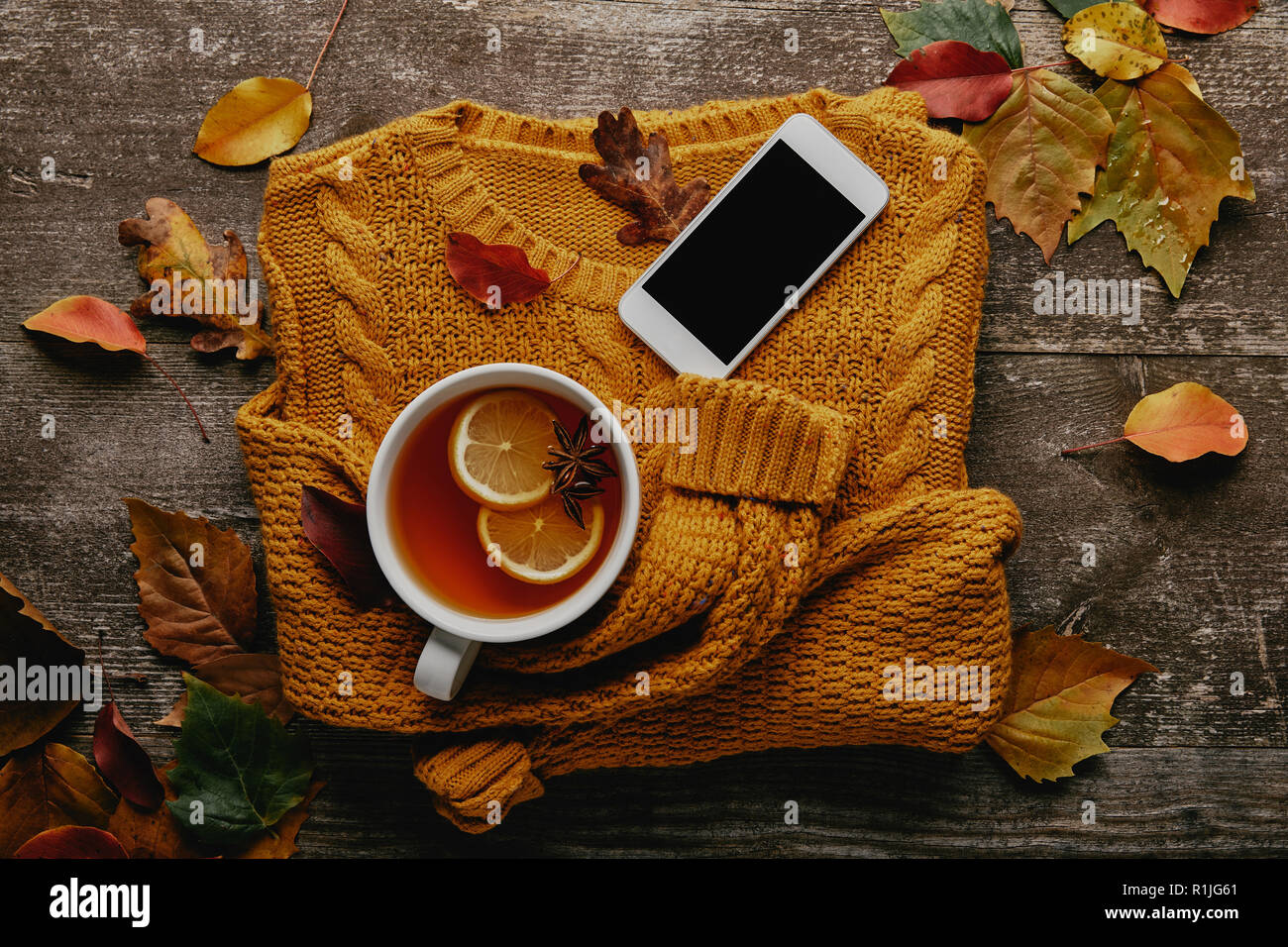 flat lay with cup of tea, ornage sweater, smartphone with blank screen and fallen leaves on wooden surface - Stock Image