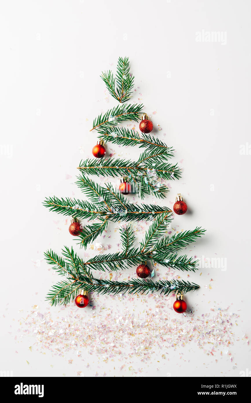 top view of green pine branch decorated as festive christmas tree with glitters on white background Stock Photo