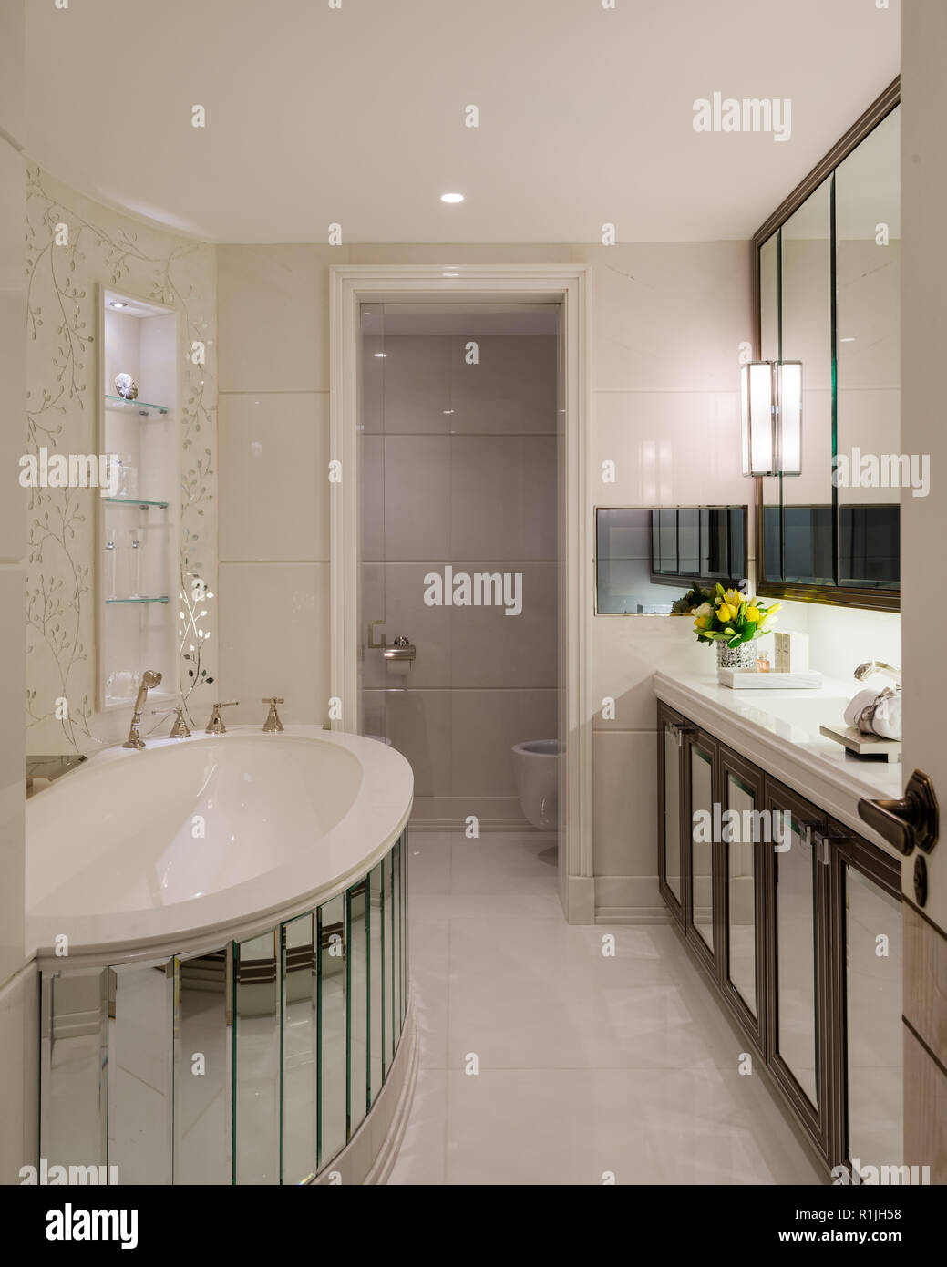 Mirrored bathtub in white bathroom - Stock Image