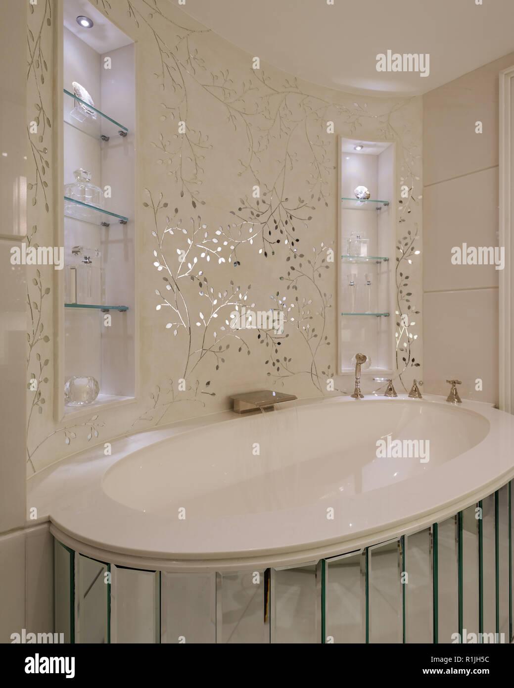 White floral wallpaper over bathtub - Stock Image