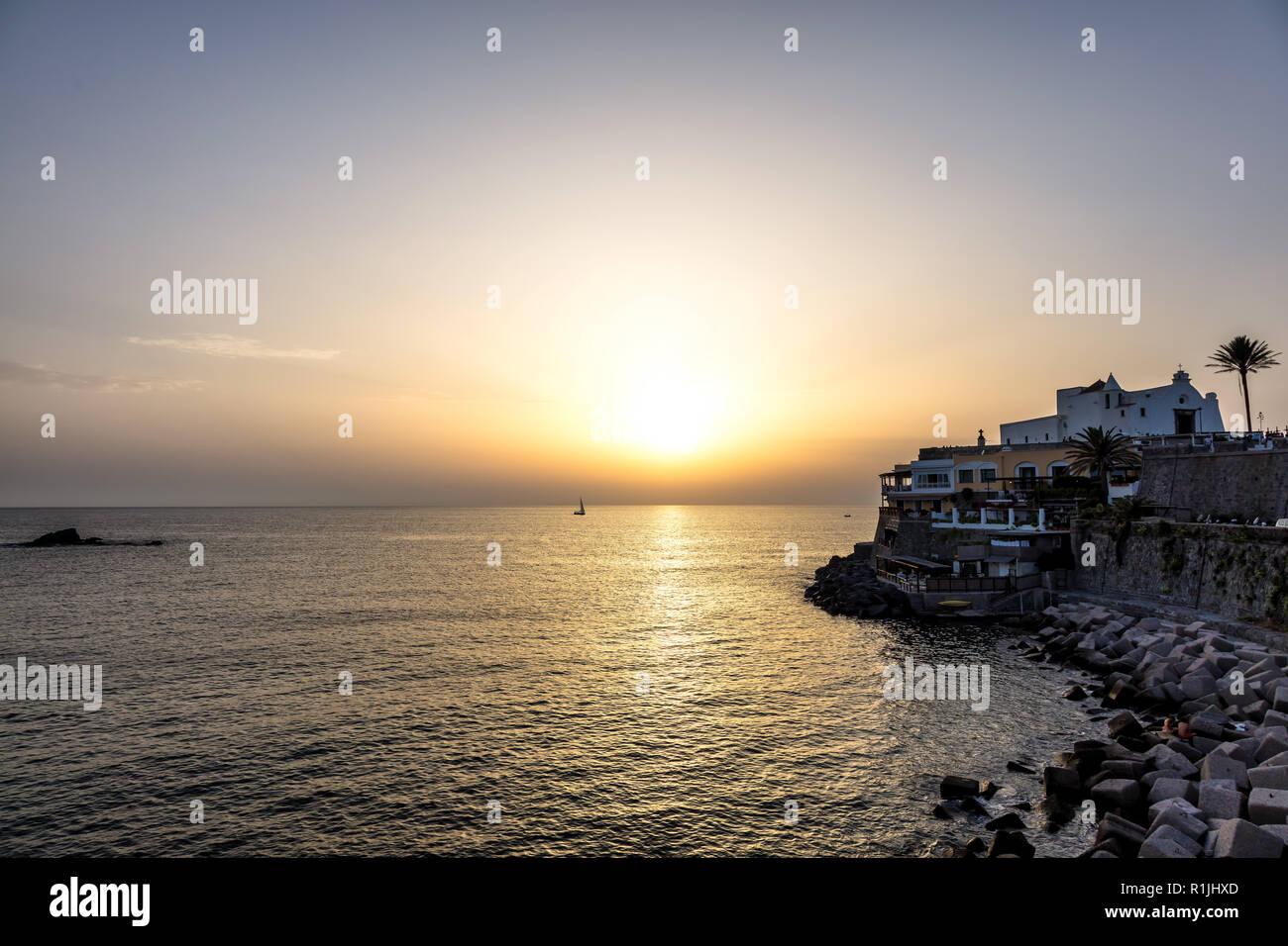 Sunset on the coast of Ischia, Gulf of Naples, Campania region, Italy - Stock Image