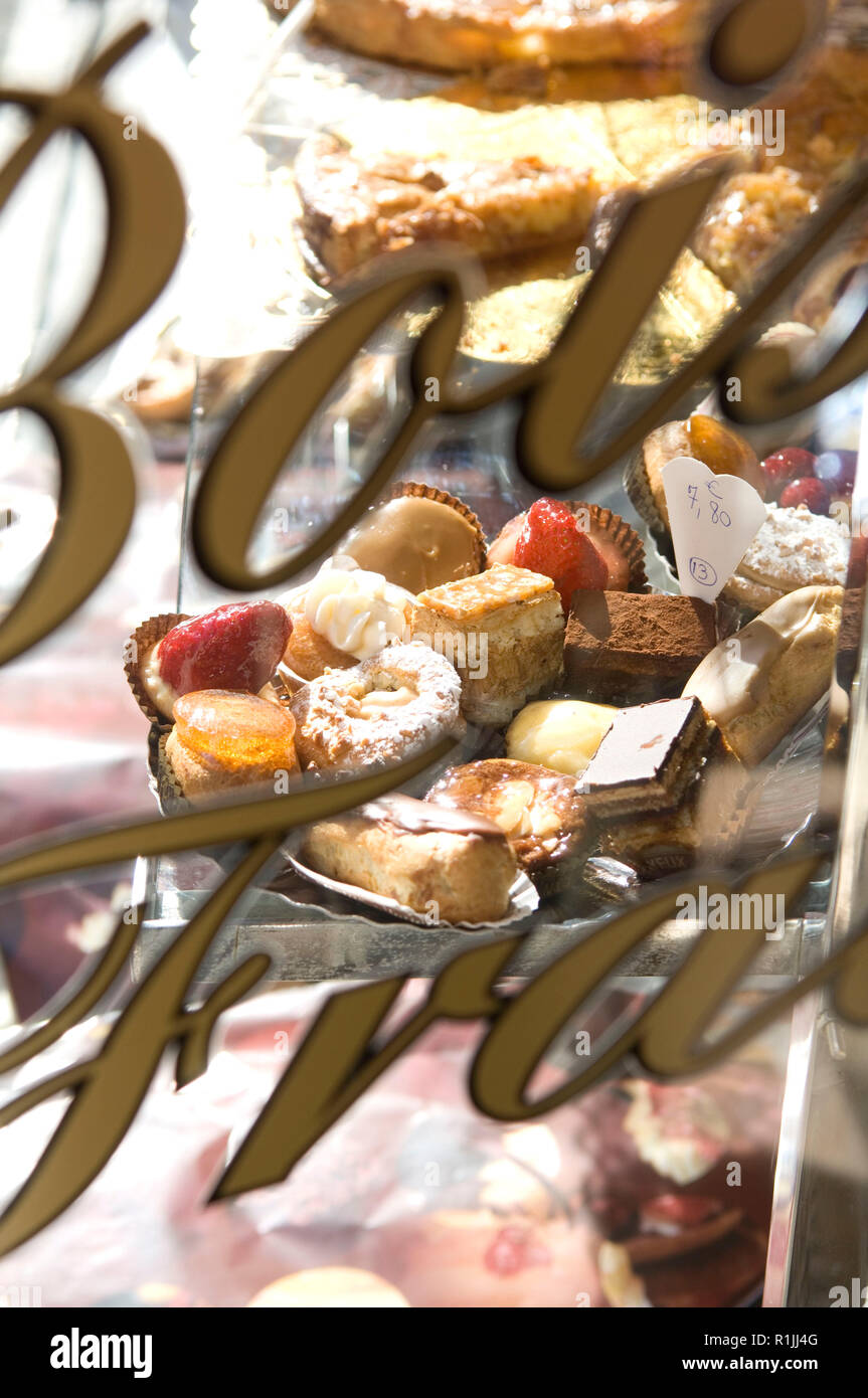 Sign on bakery window in front of desserts - Stock Image