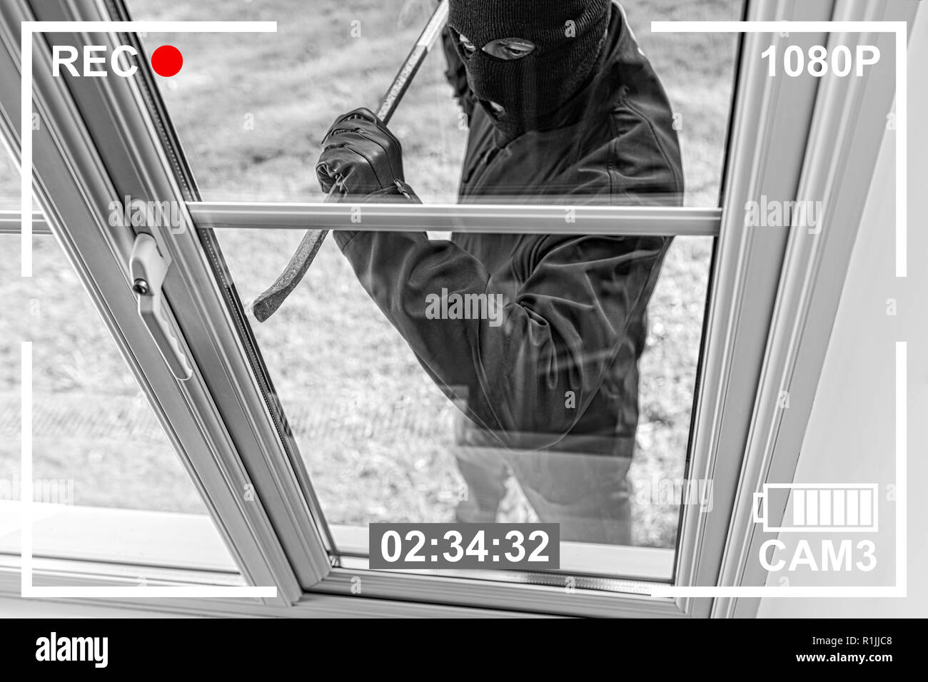CCTV view of burglar breaking in to home through window with crowbar - Stock Image