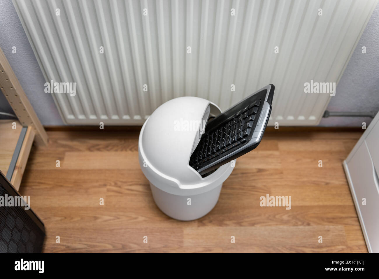 Computer Keyboard in Trash Can on Office Floor, looking down - Stock Image
