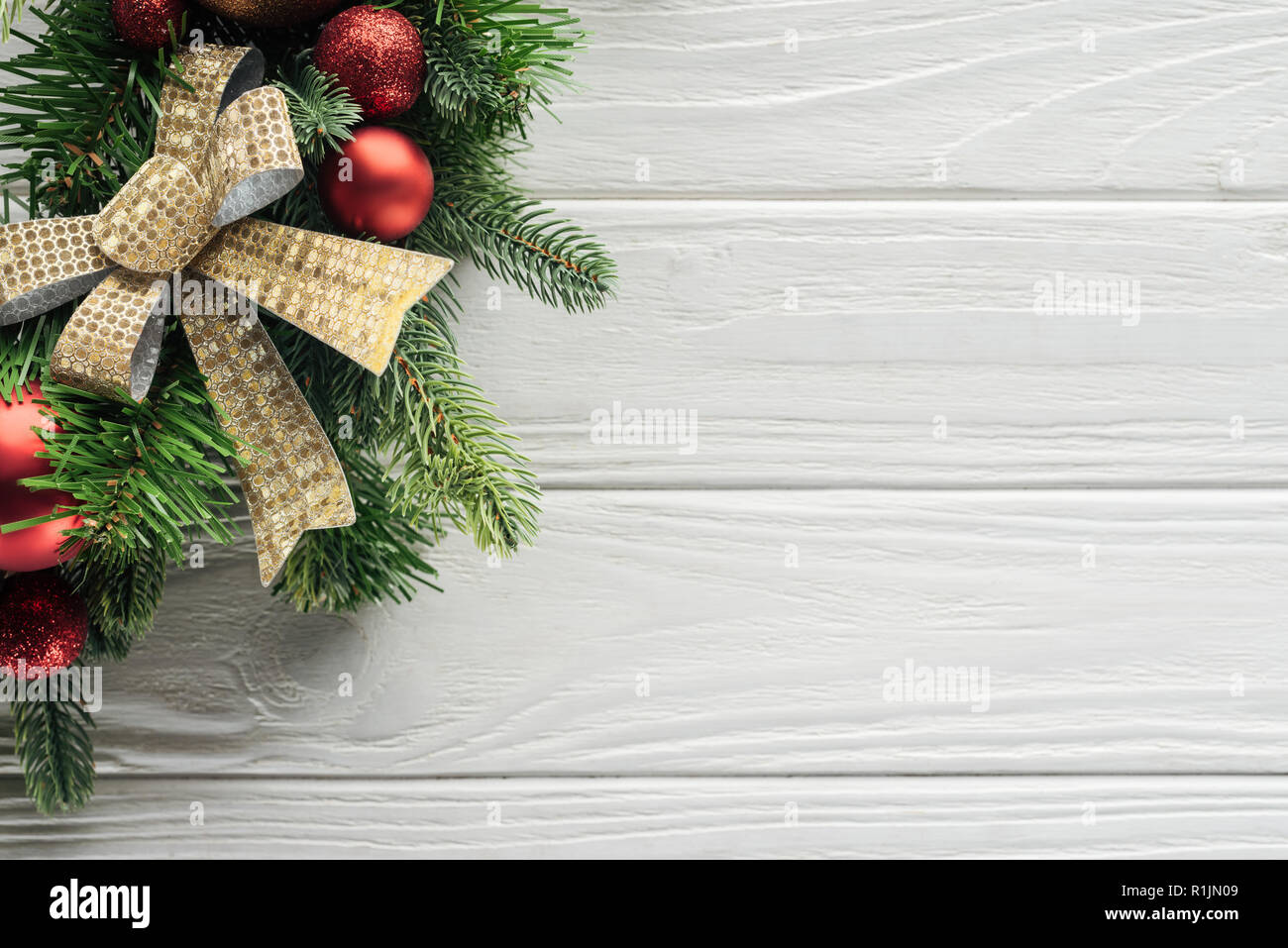 top view of wreath with red christmas toys on white wooden surface Stock Photo
