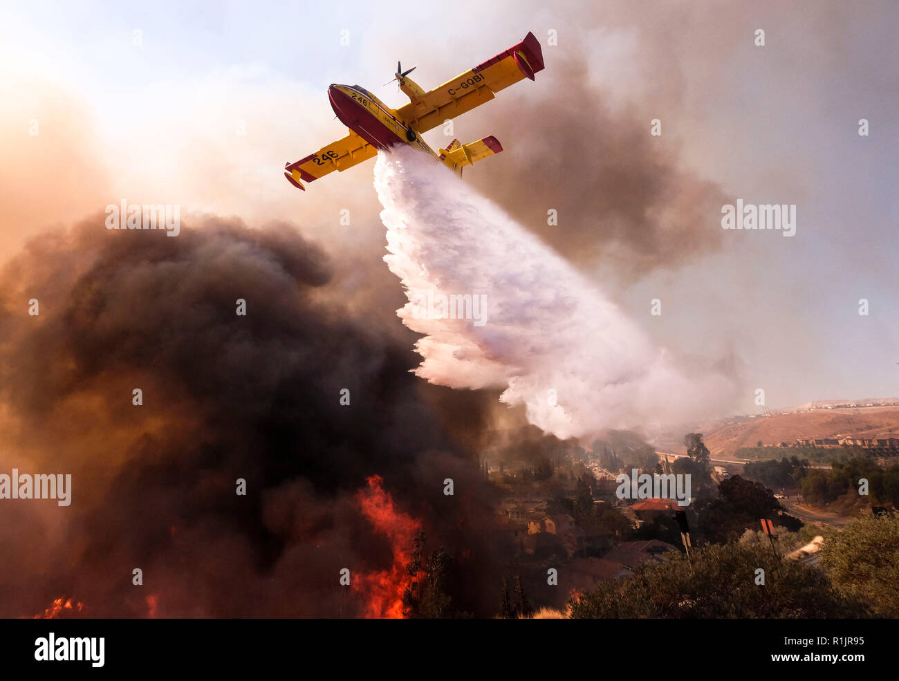 Simi Valley, California, USA. 12th Nov 2018. A small plane makes a drop on the wildfire near a freeway in Simi Valley, California, the United States on Nov. 12, 2018. The fire in Southern California continued to destroy homes. (Xinhua/Zhao Hanrong) (jmmn) Credit: Xinhua/Alamy Live News - Stock Image