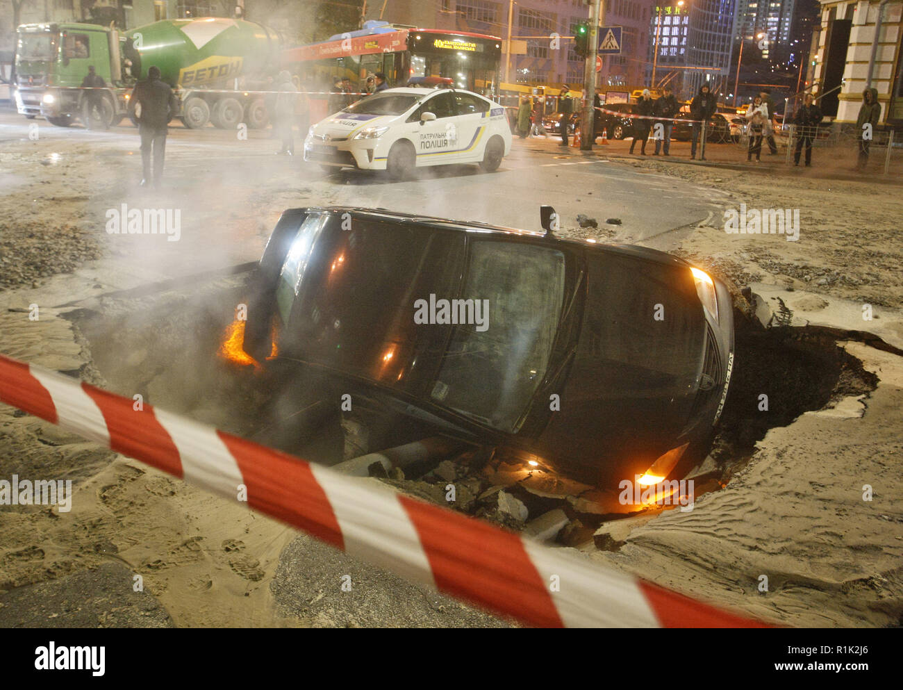 Kiev, Ukraine. 13th November 2018. A car fell in the hole in the asphalt is seen, at the side of a heat pipeline accident in center of Kiev, Ukraine, on 13 November 2018. Kyiv's downtown is paralyzed with large traffic jams, as a result of an incident occurred on the heat water pipeline, which broke and led to a transport collapse in the city. Credit: Serg Glovny/ZUMA Wire/Alamy Live News - Stock Image
