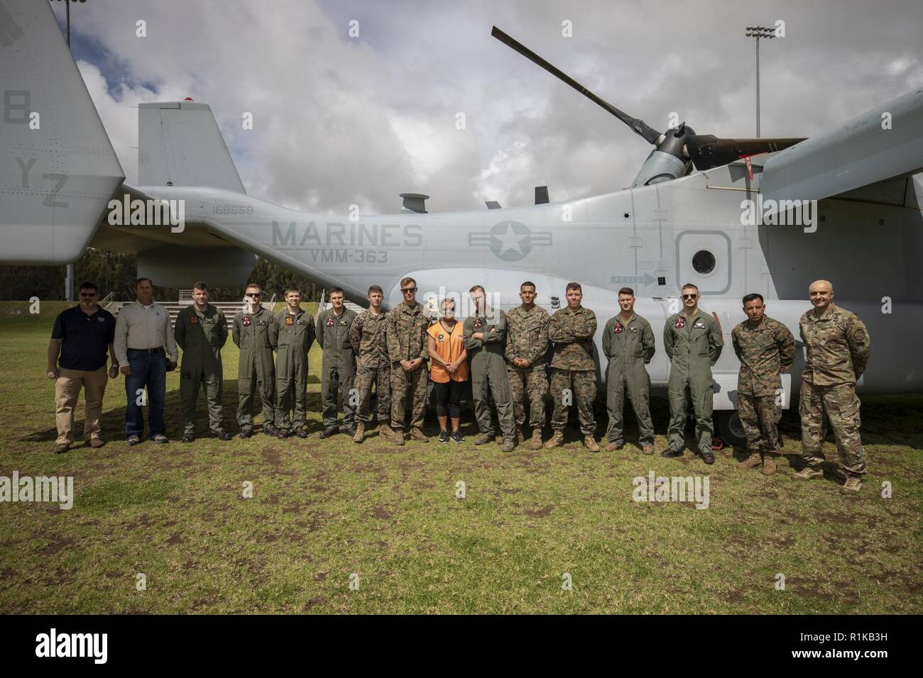 U.S. Marines with Marine Medium Tiltrotor Squadron (VMM) 363, pose for a photo with Pohakuloa Training Area military leaders and community spectators in front of a MV-22B Osprey at the Waimea District Park, Oct. 12, 2018. VMM-363, nicknamed the Lucky Red Lions, flew one of their aircraft from Marine Corps Base Hawaii on Oahu to the Waimea Fall Festival, providing a static display and subject matter experts for a first-hand experience to the festival's attendants. The squadron arrived to Hawaii earlier this year increasing the combat capability and crisis response within the Indo-Pacific region Stock Photo