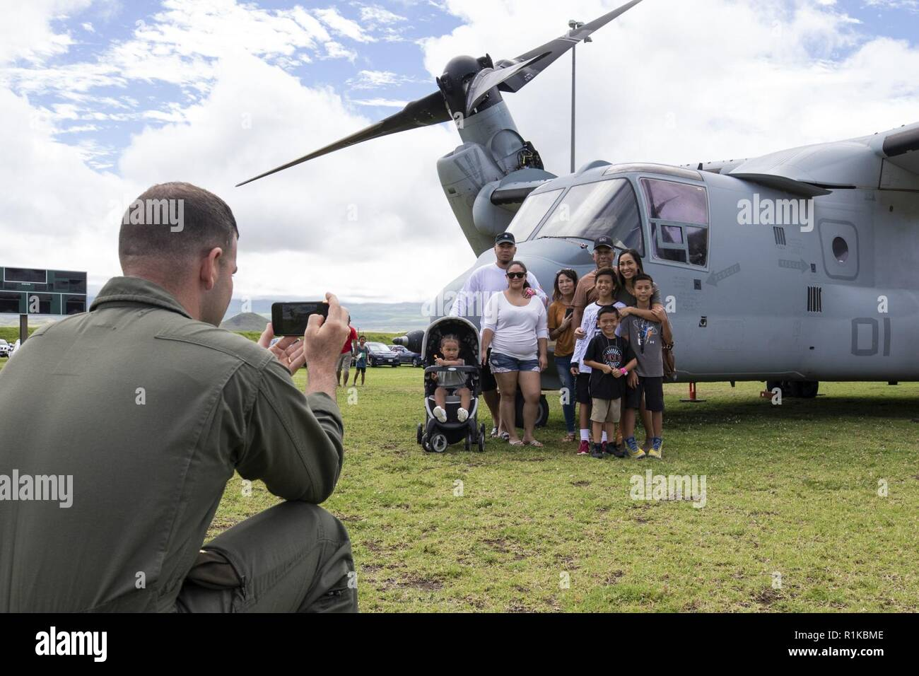 U.S. Marine Corps Maj. Christopher Ulcak, an aircraft commander with Marine Medium Tiltrotor Squadron (VMM) 363, takes a photo of local community members at the Waimea District Park in front of an MV-22B Osprey aircraft, Oct. 13, 2018. VMM-363 flew one of their aircraft from Marine Corps Base Hawaii on Oahu to the Waimea Fall Festival, providing a static display and subject matter experts for a first-hand experience to the festival's attendants. The squadron arrived to Hawaii earlier this year increasing the combat capability and crisis response within the Indo-Pacific region. Stock Photo