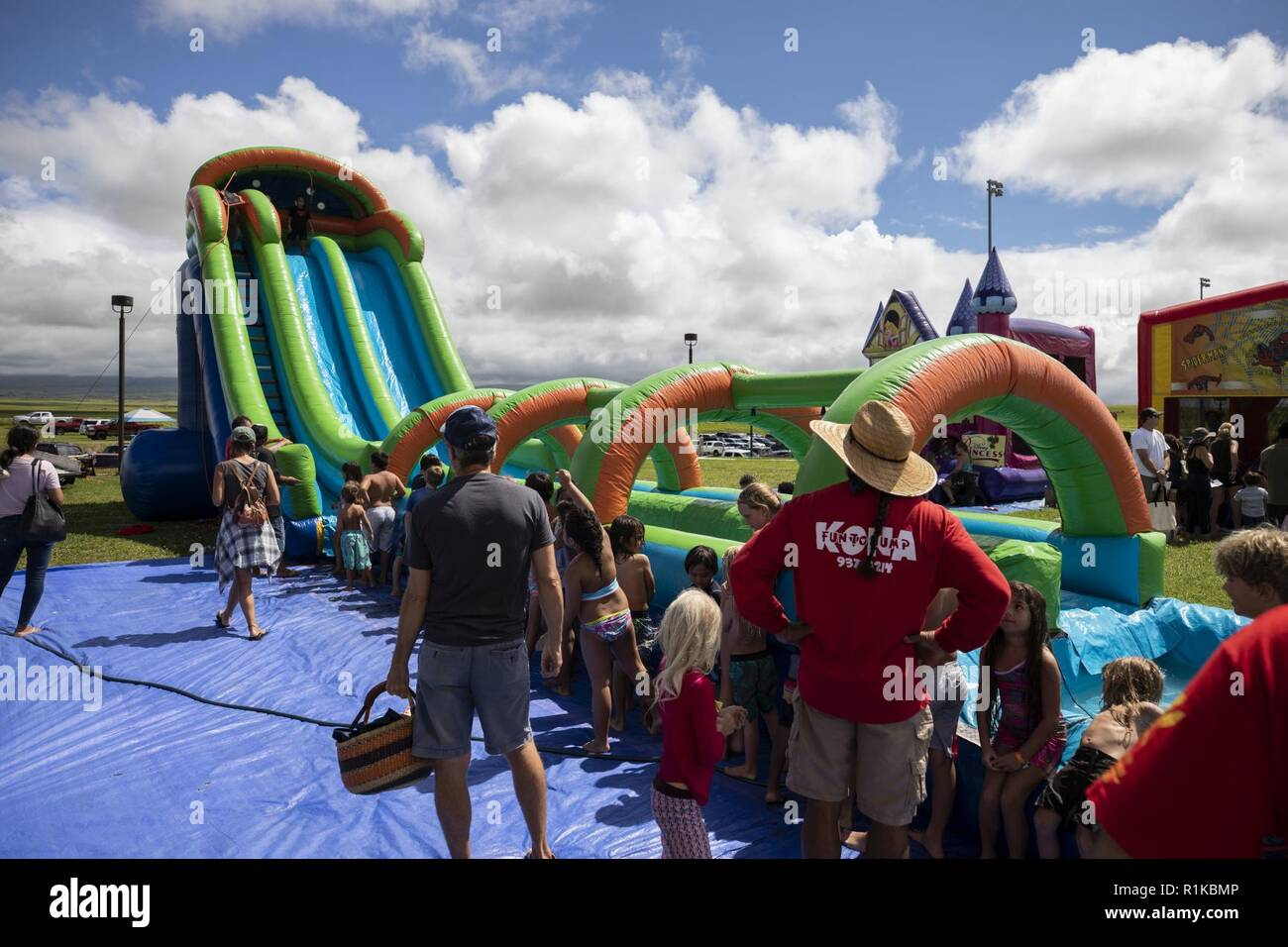 An infaltabble water slide is set up during the Waimea Fall Festival at the Waimea District Park, Oct. 13, 2018. U.S. Marines with Marine Medium Tiltrotor Squadron (VMM) 363, nicknamed the Lucky Red Lions, flew one of their aircraft from Marine Corps Base Hawaii on Oahu to the Waimea Fall Festival, providing a static display and subject matter experts for a first-hand experience to the festival's attendants. The squadron arrived to Hawaii earlier this year increasing the combat capability and crisis response within the Indo-Pacific region. Stock Photo