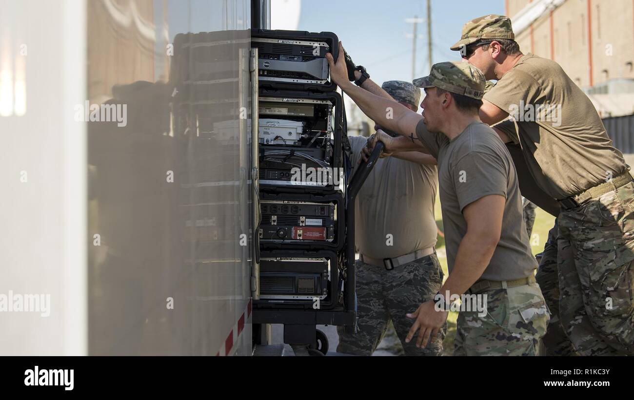 Service members from the Joint Communications Support Element and the 290th Joint Communications Support Squadron, load communication servers into a trailer before relocating to provide internet and phone capabilities to another area in need, Oct. 13, 2018, following Hurricane Michael's devastating strike. These Total Force experts can install, operate and enhance communication services and then relocate in a matter of hours, providing critical command and control whether it is for the warfighter abroad or to help our Florida family recover from the storm. Stock Photo