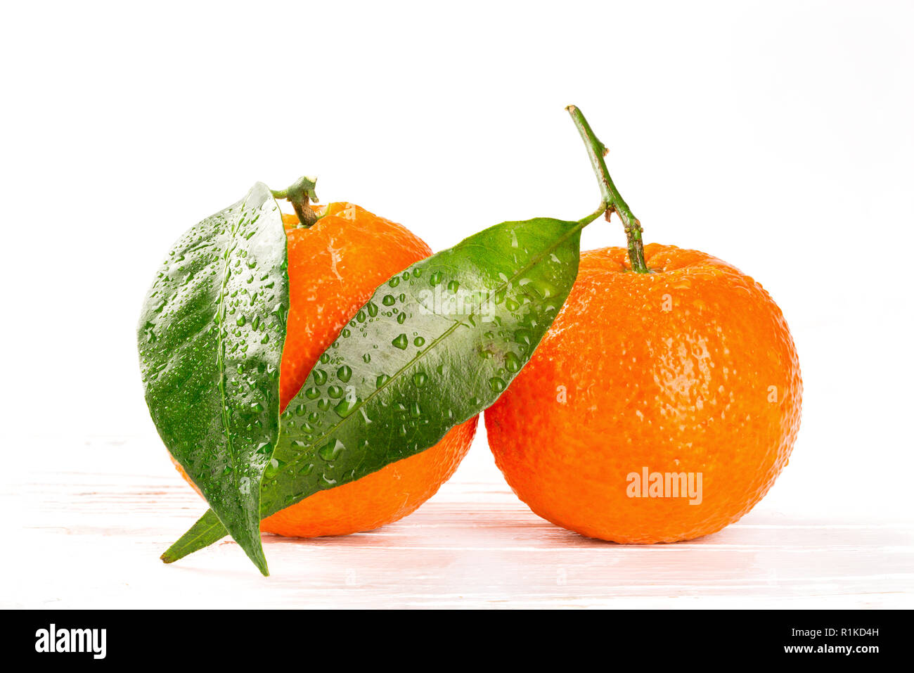 Tangerines with leaves and water drops on white wooden background, closeup - Stock Image