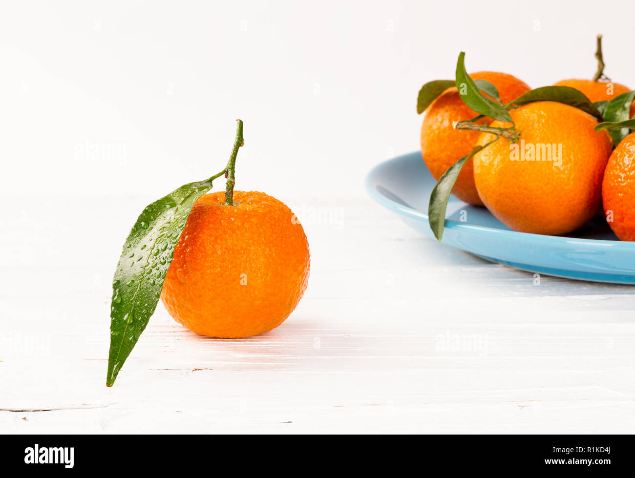 Tangerines on white wooden background with waterdrops an green leaves - Stock Image