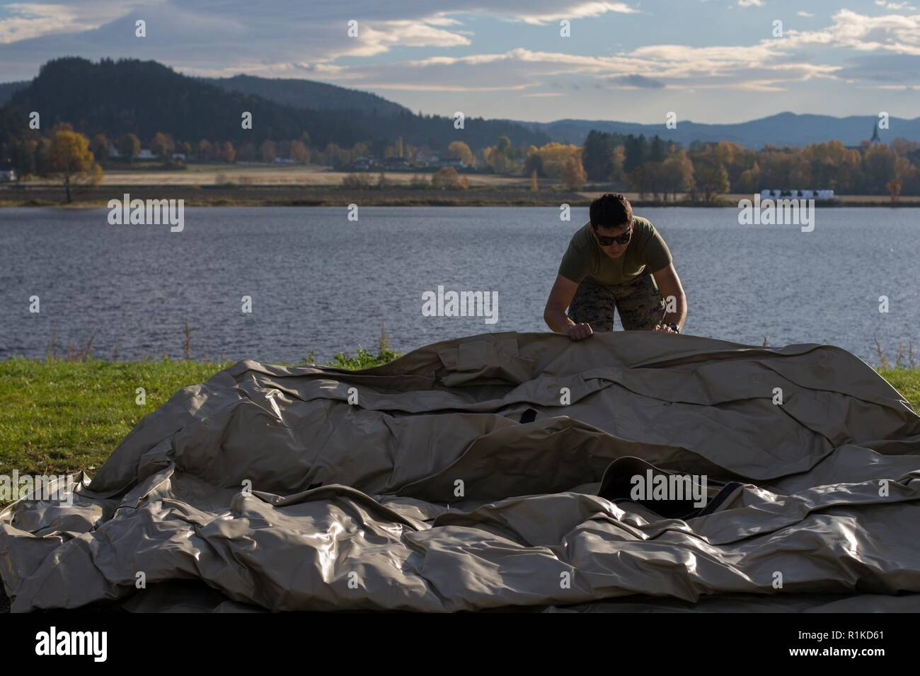 U.S. Marine Corps Lance Cpl. Israel Santibanez with 8th Engineer Battalion, 2nd Marine Logistics Group-Forward, unfolds a water storage bladder in Værnes, Norway, Oct. 12, 2018. Marines purified water and made potable for use in camp support and operations during Exercise Trident Juncture 18. Trident Juncture enhances the U.S. and NATO Allies' and partners' abilities to work together collectively to conduct military operations under challenging conditions. - Stock Image