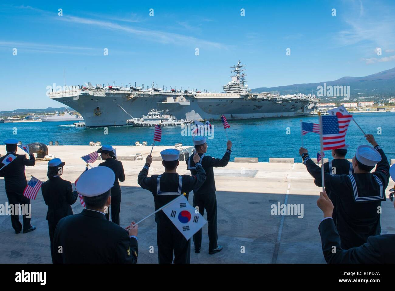 JEJU ISLAND, Republic of Korea, (Oct. 12, 2018) The Nimitz-class nuclear-powered aircraft carrier USS Ronald Reagan (CVN 76) conducts a 180 degree turn while pulling into port at the Republic of Korea (ROK) Navy base in Jeju. Ronald Reagan is forward-deployed to the U.S. 7th Fleet area of operations in support of security and stability in the Indo-Pacific region. Stock Photo