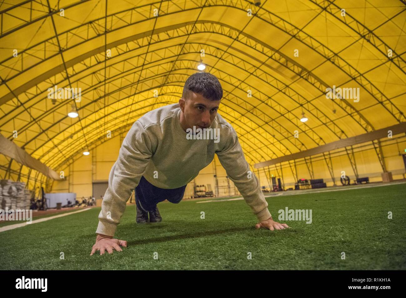 Staff Sgt. James Guardiano, 50th Civil Engineer Squadron operations management, readies for a push up inside the Indoor Running Track at Schriever Air Force Base, Colorado, Oct. 11, 2018. The IRT features newly installed heating socks which retain heat and warms the overall temperature of the facility for indoor fitness assessments. - Stock Image