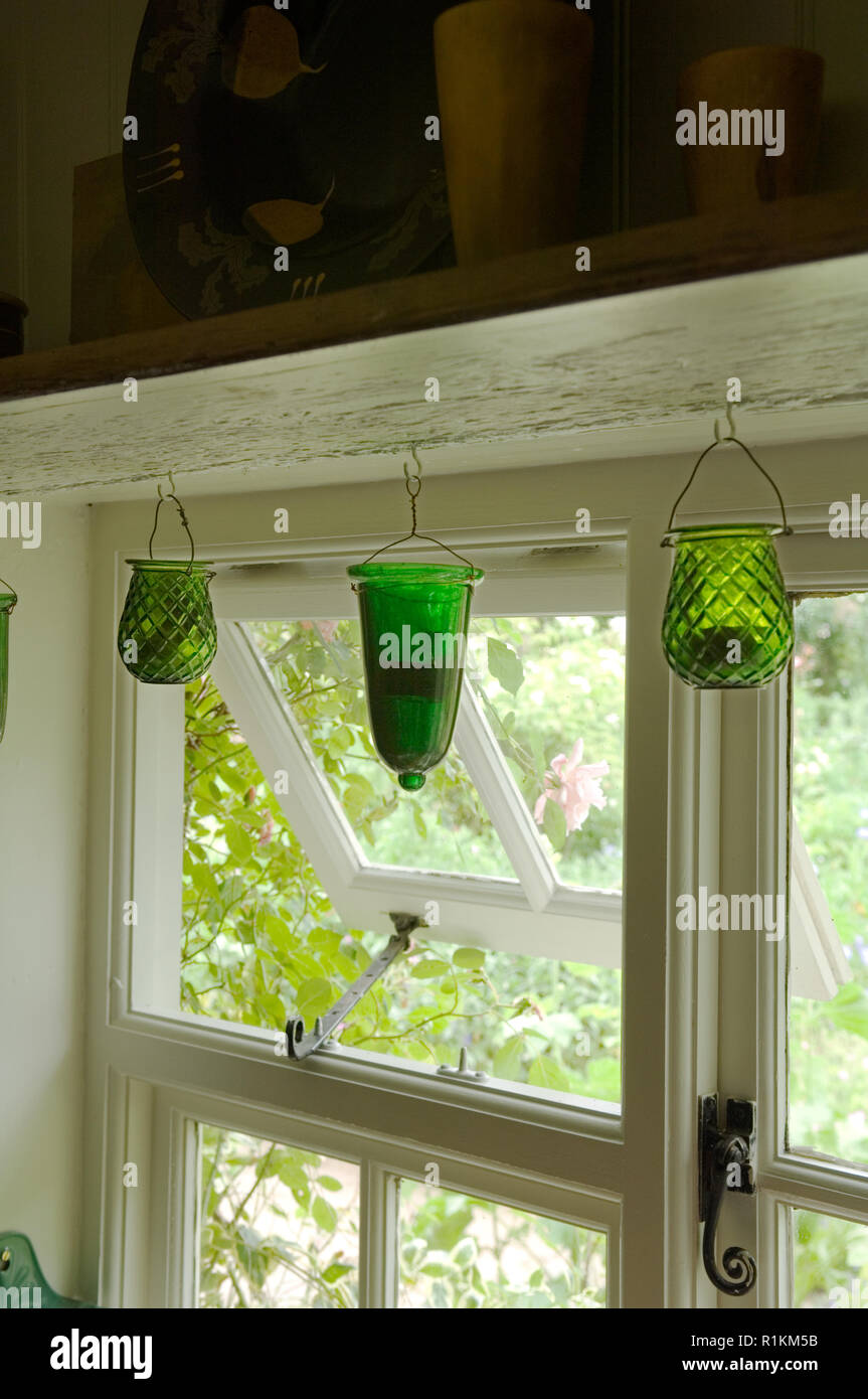Green candle holders hanging by window - Stock Image