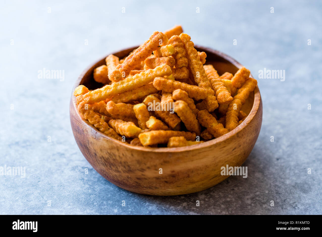 Orange Cheese Flavored Corn Snacks in Stick Shape / Roasted Chips or Salty Crackers in Wooden Bowl. Organic Roasted Snacks. - Stock Image