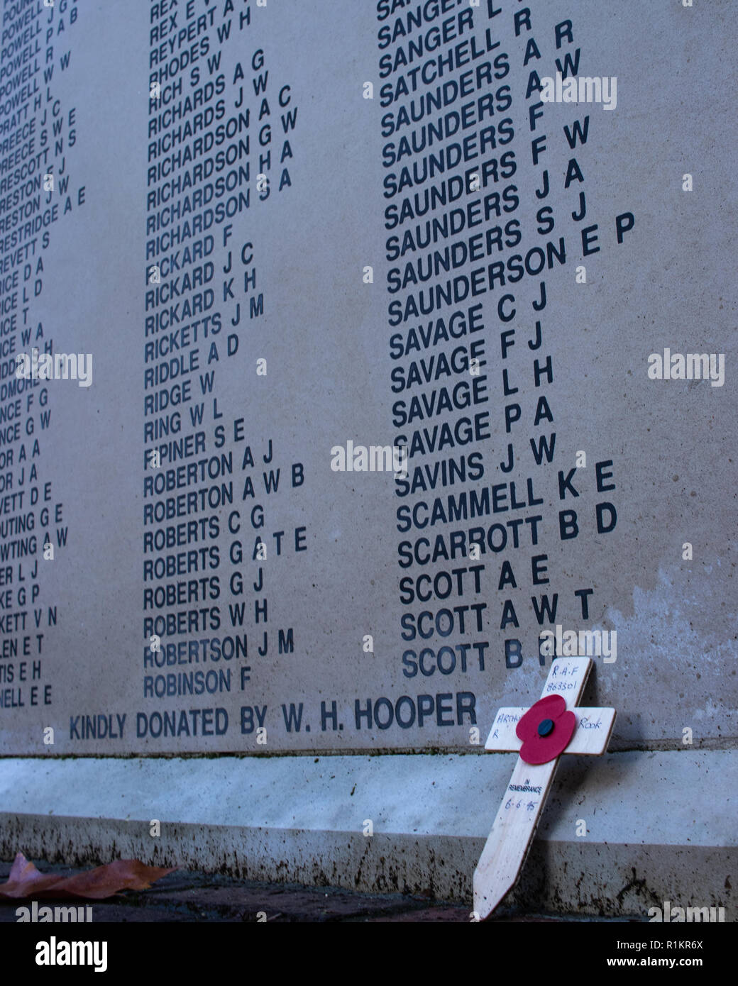 A remembrance day poppy and cross laid in front of the names writted an a war memorial - Stock Image