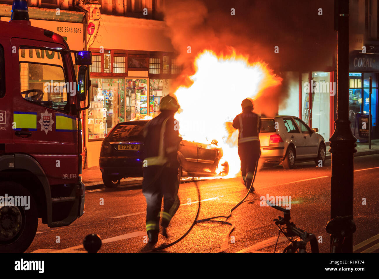 London Fire Brigade officers tackle a vehicle fire in Crouch End, North London, UK, November 2012 - Stock Image