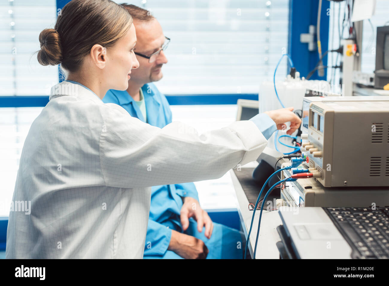 Team of electronic engineers testing a product prototype on test bench in the lab Stock Photo