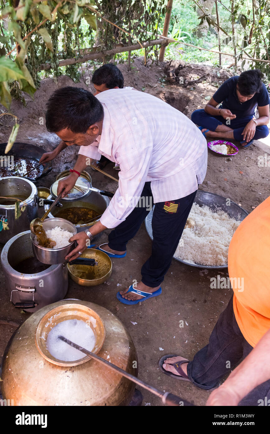 The man prepares dinner for wedding guests in the Indian village - Stock Image